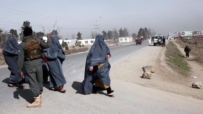 Afghaanse vrouwen in boerka en een Afghaanse agent in Kunduz, in maart vorig jaar.