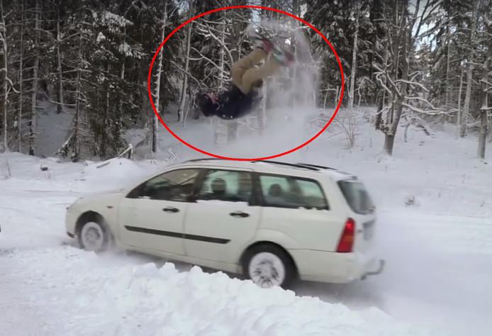 De snowboardbackflip over een auto.