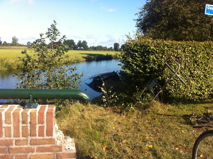 Door onbekende oorzaak is de auto hier vanaf de weg, langs het bruggetje in het Toevoerkanaal bij Terwolde terecht gekomen.