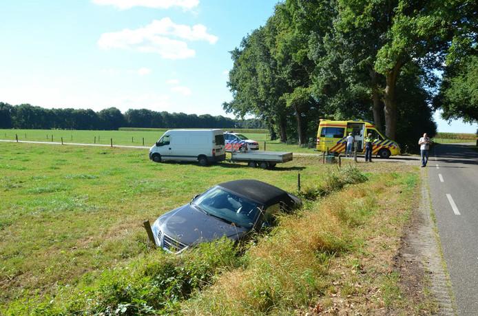 De auto in het weiland met op de achtergrond de hulpdiensten.