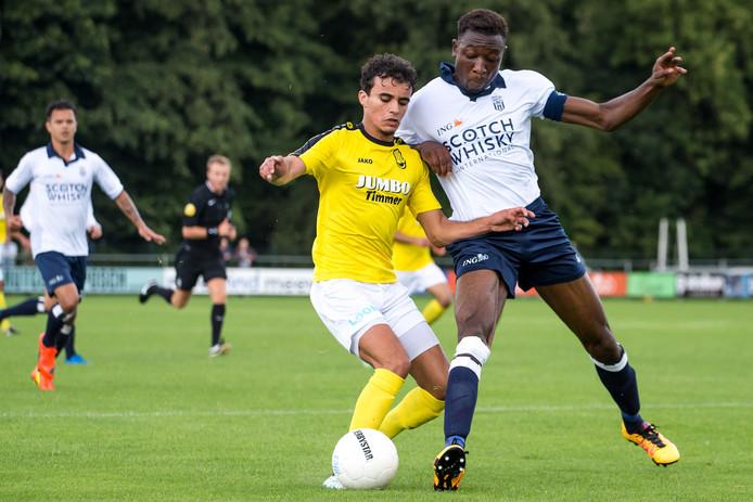 Mohammed Bendadi (l) in duel met HFC-speler Carlos Opoku (r).