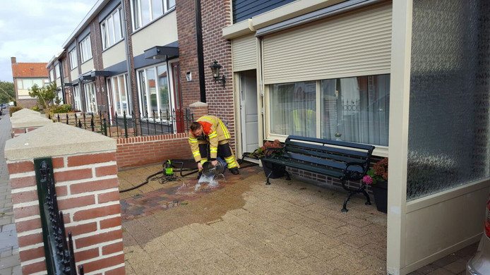 Brandweerlieden proberen het water in de woning aan de Pijlkruidstraat weg te zuigen.