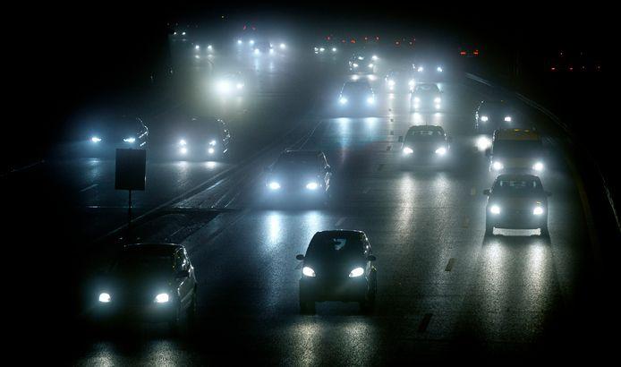 Foto ter illustratie. Auto's rijden in de avondspits op de A12 door een dikke laag mist naar huis.