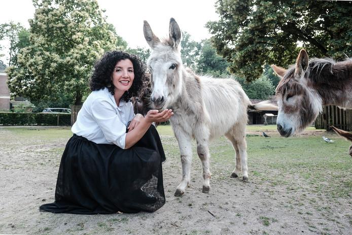 Nadia Zerouali in de wei bij de ezels op kinderboerderij Frerikshof in Winterswijk.