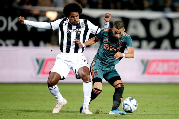 Hakim Ziyech draait in het eerste duel van Ajax met PAOK  weg bij Diego Biseswar.