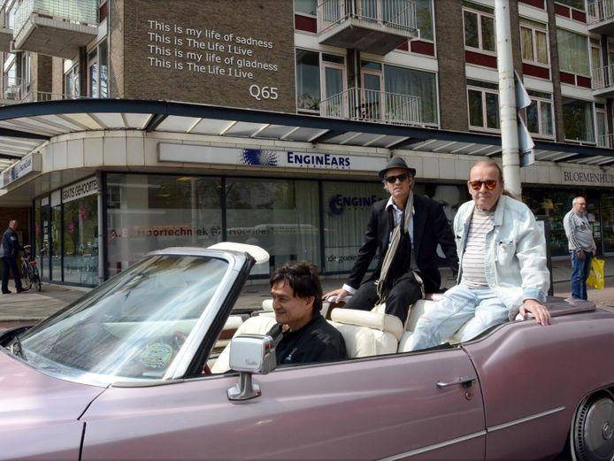 Op de gevel van een flat op het Almeloplein wordt in 2016 een tekst onthuld van de Haagse band Q65 die opgroeide in de buurt. Q65-gitarist Joop Roelofs (uiterst rechts) rijdt er in een sportwagen langs.