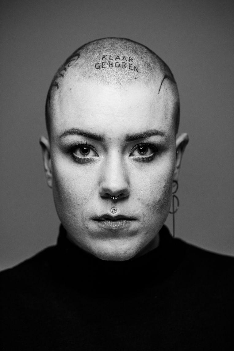 """Emilie. """"Toen ze vroegen aan Emilie of ze klaar was voor haar nieuwe tattoo op de zijkant van haar hoofd was het antwoord dat ze klaar geboren is. Ze heeft die woorden dan ook maar ineens maar op haar voorhoofd laten tatoeëren."""""""