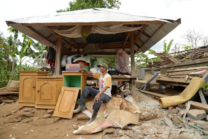 Een vrouw voert voor haar vernielde huis een gebedsceremonie uit, terwijl haar man gelaten op de puinhoop zit met wat spulletjes die hij nog kon redden.