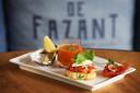 Het kleurrijke voorgerecht van het maandmenu: Zomerproeverij met een oester, gazpacho, bruchetta en parmaham.