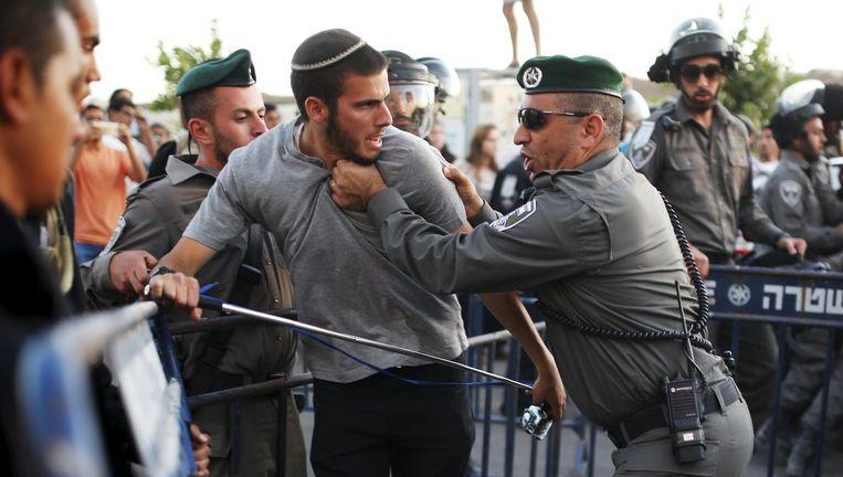 Een Israëlische agent grijpt een Joodse kolonist vast tijdens de rellen. Beeld REUTERS