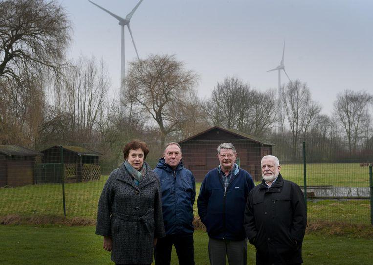 Leden van Actiegroep Beter Buurt Puurs - Linda Decat, Luc Boel, Guido Van Campenhout en Marcel Van Tricht - in een tuin die uitkijkt op de windmolens.