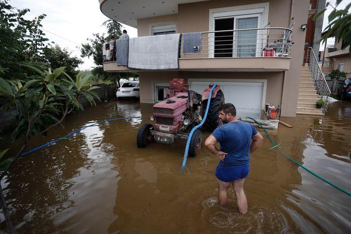 Bewoners in Kavalari proberen het regenwater weg te pompen