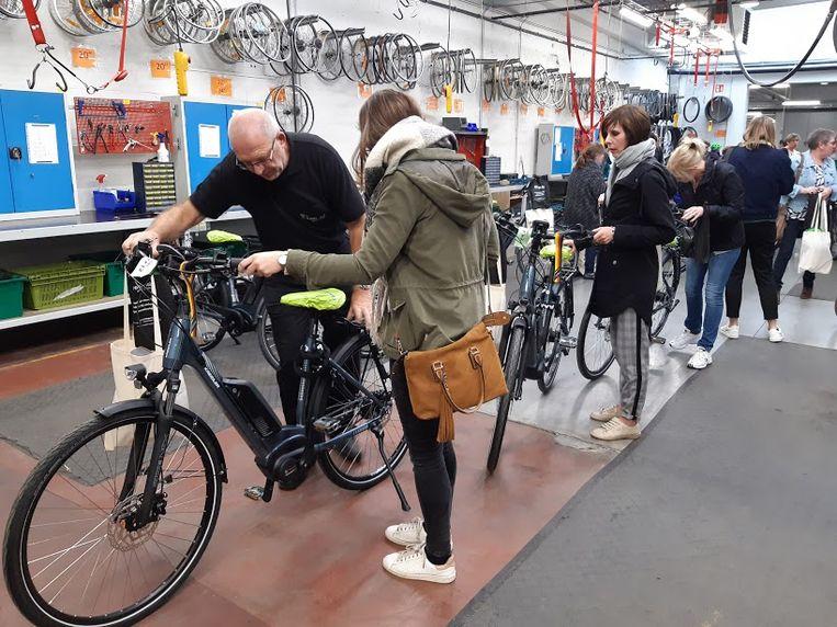 De medewerkers van Familiezorg Oost-Vlaanderen halen hun elektrische fiets op bij Trans-Fair in Gent.
