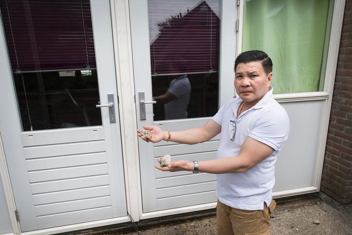 Phoa Truong laat wat stenen zien die tegen zijn ruiten zijn gegooid.