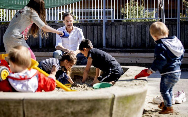 Minister-president Mark Rutte bezoekt een kinderopvang. Medewerkers zorgen er voor kinderen van ouders met vitale beroepen.  Beeld ANP
