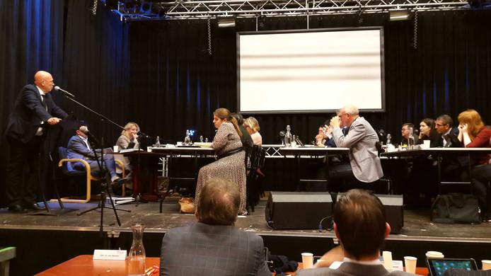 Wethouder Dick van Zanten (links) geeft de raad op het podium van PoGo uitleg over de begroting. Volgens de oppositiepartijen  'faalde de wethouder financiën bij de beantwoording in zowel eerste als tweede termijn'.