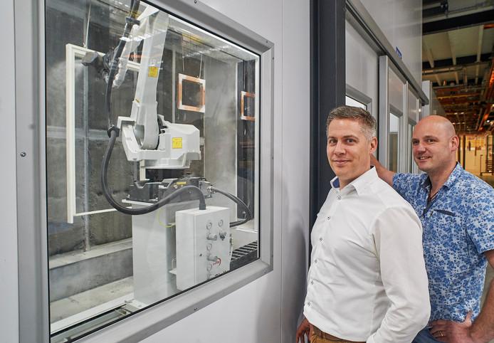 De nieuwe spuitrobot behandelt een kozijn. Daarnaast Ferry Peters en rechts Patrick Habraken.