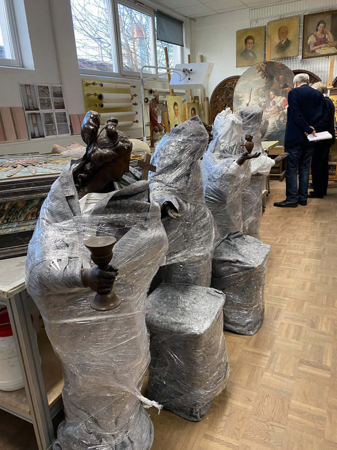 De Wouwse heiligenbeelden en hun consoles in het Duits museumatelier in Paderborn. Daar worden ze opgeknapt voor de expositie. Links vooraan Fides (geloof), een van de drie theologische deugden. Het vrouwenfiguur houdt een kelk, een boek en een kruis vast. Met haar rechtervoet staat ze op een draak (symbool voor ongeloof of de duivel. Gemaakt door Ludovicus Willemsens.