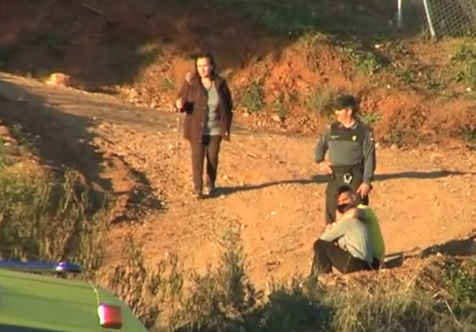 Julens vader José (r) en moeder Vicky (l) met een Spaanse politieman bij de plek waar hun zoontje verdween.