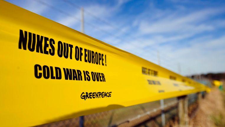 Beeld van een protestactie van Greenpeace aan de omheining van Kleine Brogel.
