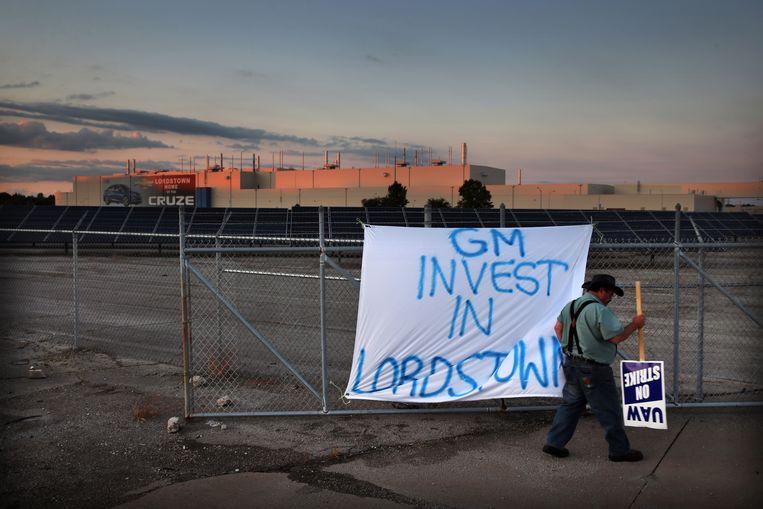 Een medewerker van United Auto demonstreert bij het hek van de oude fabriek van General Motors in de buurt van Lordstown, Ohio.  Beeld Boston Globe via Getty Images