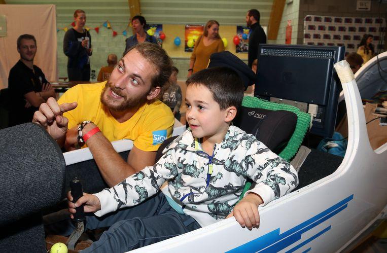 Deze jongen leert zweefvliegen in een simulator.