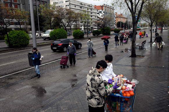 Mensen schuiven aan voor een supermarkt in Madrid; ze laten voldoende afstand tussen.