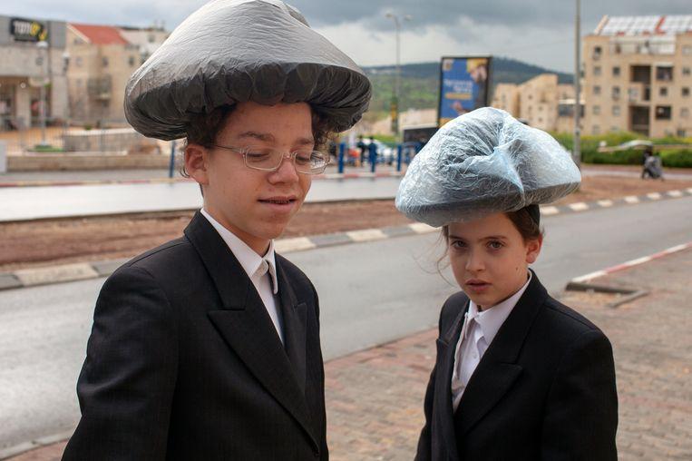Twee haredi-jongens beschermen hun hoeden tegen de regen met plastic zakjes. Beeld Geert van Kesteren