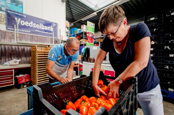 Vrijwilligers sorteren paprika's bij de voedselbank.
