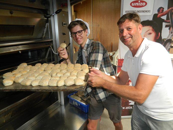 Bakker Vincent Gozin en winnaar Bram steken samen de broodjes in de oven.
