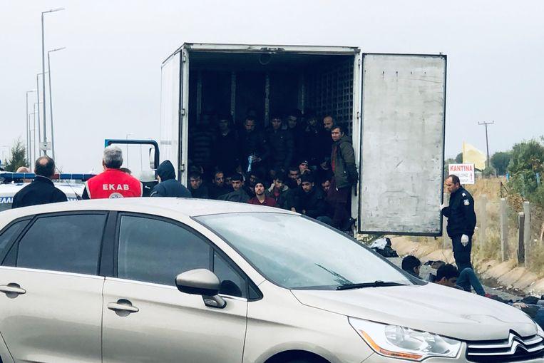 De migranten worden uit de koelwagen gehaald.