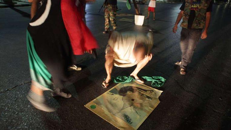 Rebellen stampen op een poster van Muammar Kaddafi in de Libische hoofdstad Tripoli. Beeld afp