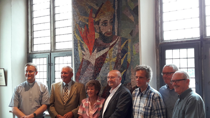 Norbertus kijkt vanaf zijn mozaïek in de raadszaal van Gennep toe terwijl pastoor Guido Kessels, burgemeester De Koning, abt Denis Hendrickx, Mieke Hoogkamp-Korstanje, André Vermeulen, Frank Meeuws en Ted Noij op de foto gaan.