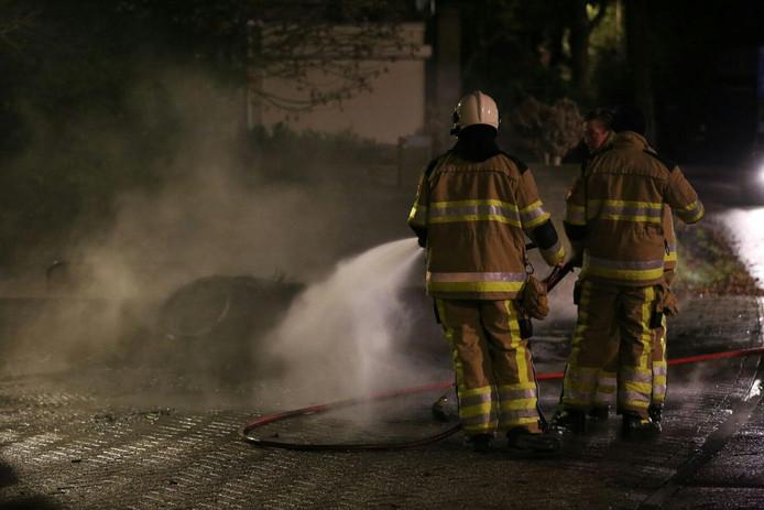 De brandweer aan het werk bij de autobanden in Waardenburg.