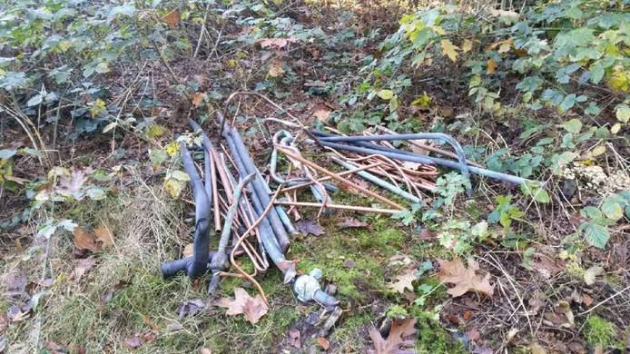 Leidingen en kranen lagen voor oud vuil in het bos.