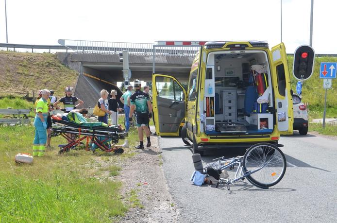 Veel omstanders bekommeren zich om het slachtoffer. Zijn fiets is zwaar beschadigd.
