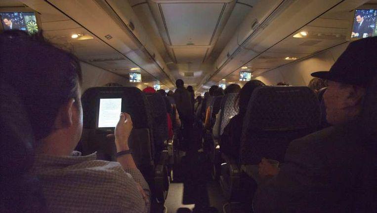 Passagiers gebruiken hun telefoons aan boord van een vlucht van American Airlines. Beeld reuters