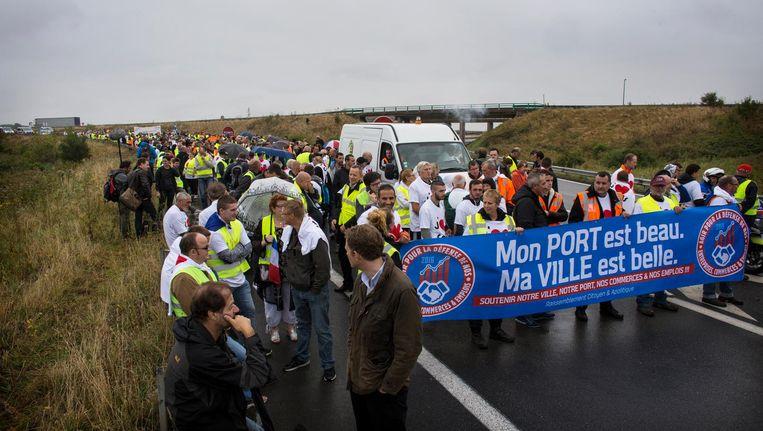 Vrachtwagenchauffeurs, havenwerkers en boeren demonstreren tegen de Jungle van Calais door middel van een wegblokkade op de A16. Beeld Bart Koetsier
