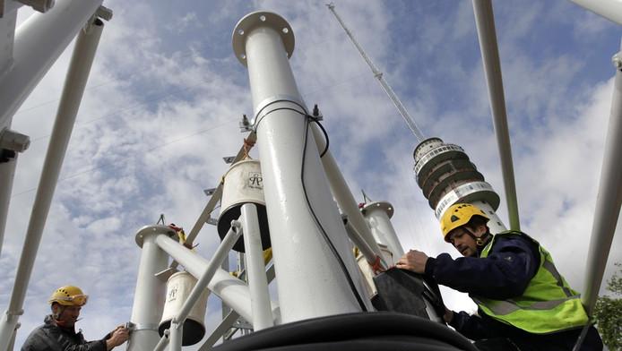 Bouwvakkers werken aan de zendmast in het Drentse Hoogersmilde. De zendmast wordt na een verwoestende brand in juli vorig jaar herbouwd.