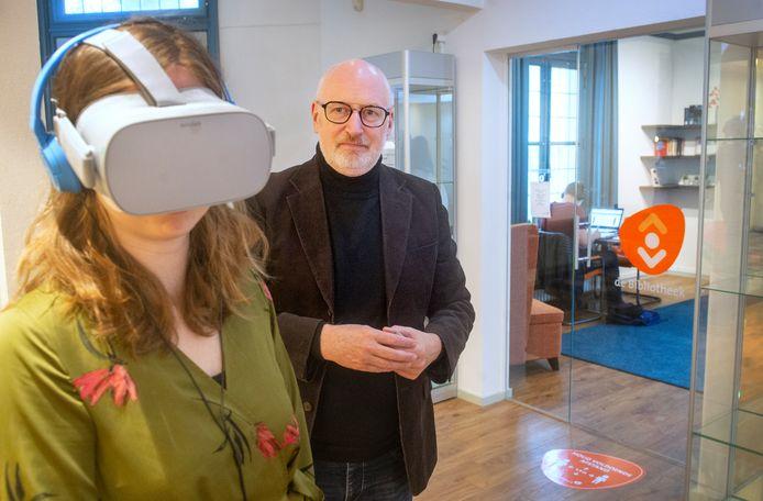 Marcel Eijkemans met de dementiebril in de bibliotheek te Veghel. Jolijn van Rossem van Bibliotheken Meierijstad draagt de virtuele bril.