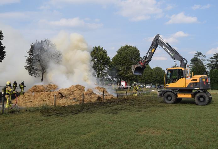 Terwijl een graafmachine het brandende hooi uit elkaar trekt, blussen brandweermannen het vuur.