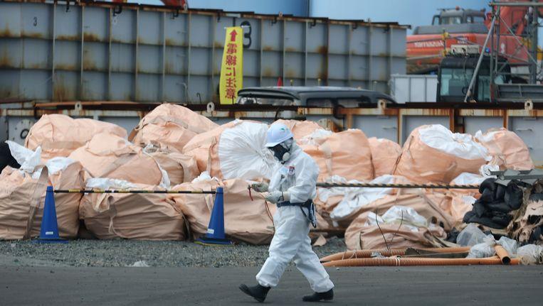 Een arbeider wandelt voorbij stapels radioactief afval in de kerncentrale van Fukushima.