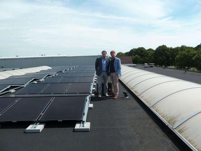 Links directeur Yvar Monasch van Best Wool Carpets en rechts Ralf Klop bij de zonnepanelen op de bedrijfshallen van het bedrijf.