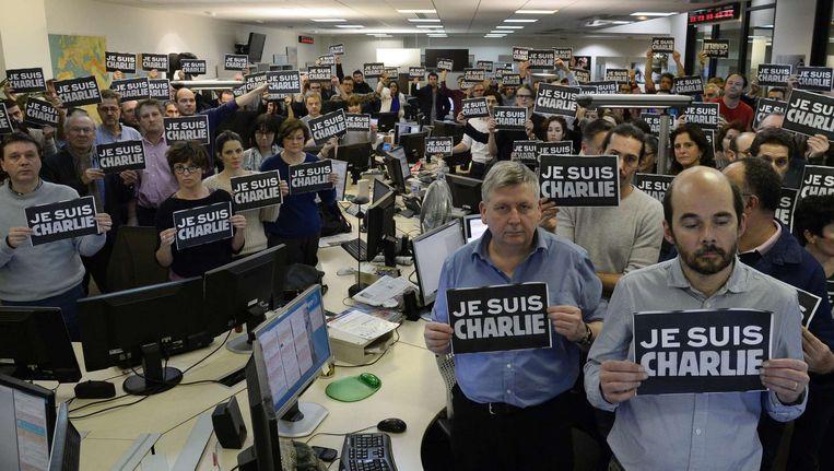 De redactie van de Agence France Press houdt bordjes met de tekst Wij zijn Charlie omhoog Beeld AFP