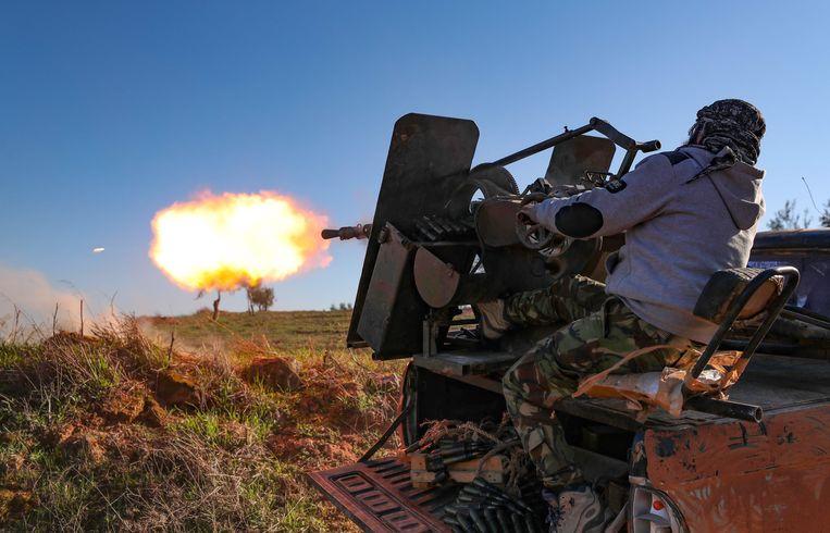 Een door Turkije gesteunde Syrische strijder schiet in de richting van Saraqeb. Beeld AFP