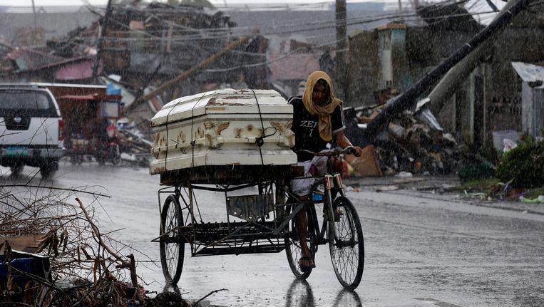 Een Filipino vervoert door de regen in Tacloban een lijkkist voor de begrafenis van een dierbare. Beeld epa