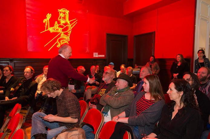 Dominee Gremdaat (Paul Haenen) praat met mensen in de zaal over de staties van Horror Vacui. Op de achtergrond: het  neonwerk statie IX