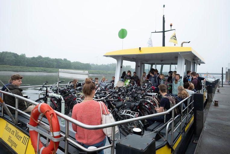 De overzetboot zit overvol, vooral de fietsen nemen veel plaats in beslag.
