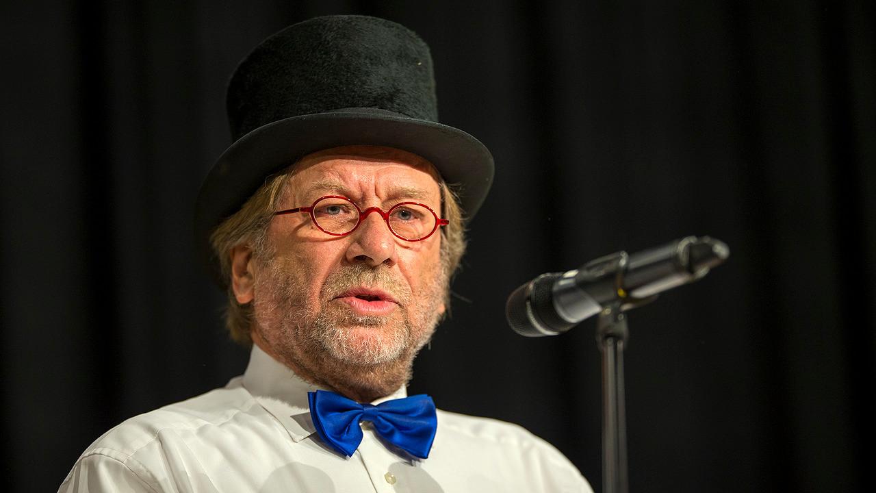 Louis van den Bosch zoals velen hem herinneren, op een podium achter een microfoon.