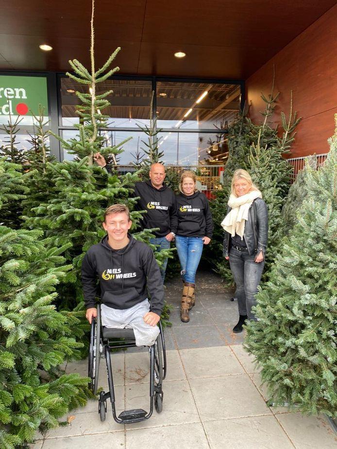 Niels en zijn moeder krijgen de eerste kerstboom uit handen van John van Hout en Jeanette van Dommelen